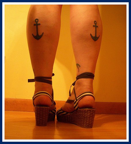Lady anchor tattoos on both legs
