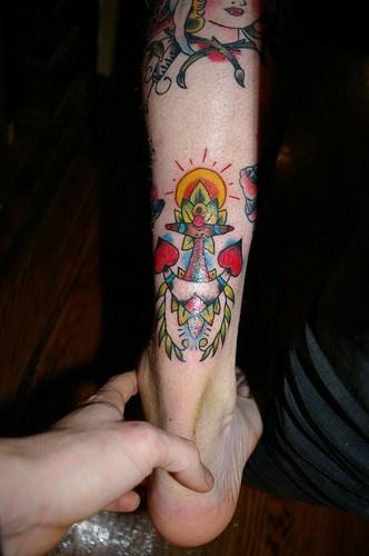Ancora impressionante con sole e fiori tatuata sulla gamba