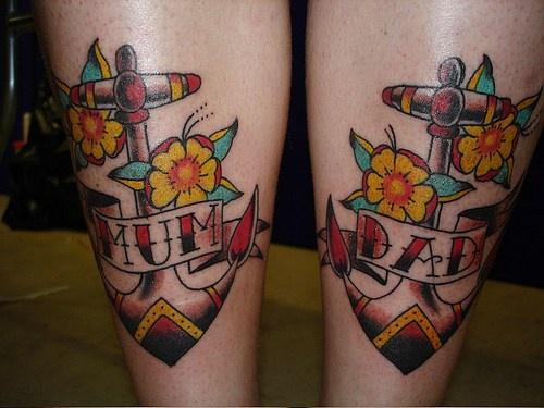 Tatuaje En Ambos Piernas Anclas Con Flores Para Mamá Y Papá
