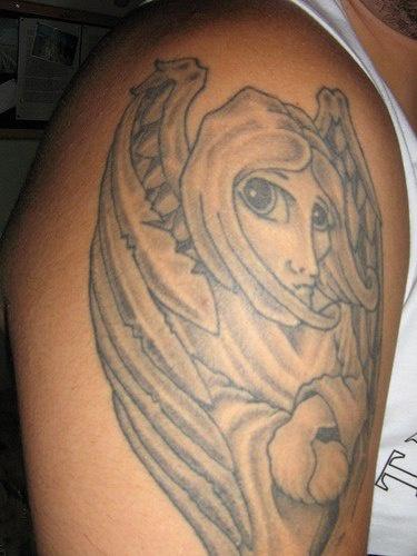 Angelo strano con gli occhi grandi  tatuato sul deltoide