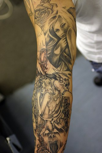 Full sleeve tattoo with angel and demons