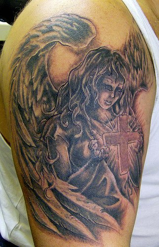 ragazza con le ali tiene in mano la croce tatuaggio opera d&quotarte