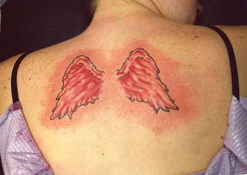 Small red angel wings tattoo
