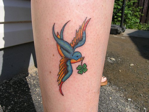 Bird with green leaf ankle tatto
