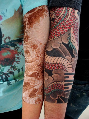 Red designed  tail arm tattoo