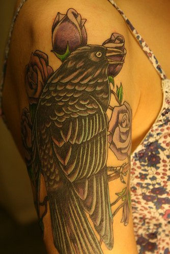 Black crow and roses arm tattoo