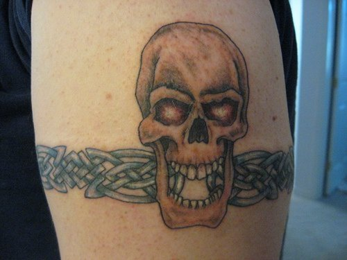 Skull with opened mouth  arm tattoo