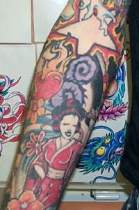Geisha con i fiori e la stella argenteo tatuati