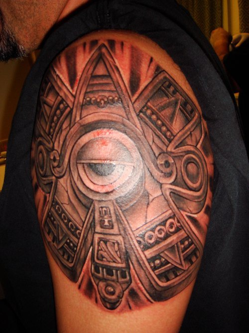Sun stone with eye tattoo on shoulder