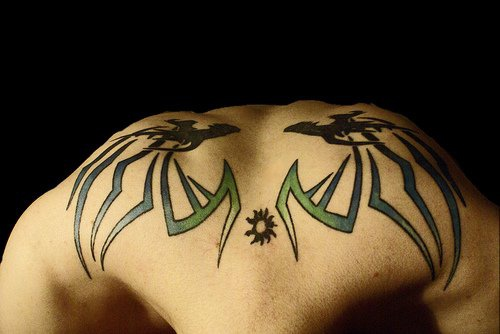 Two  similar monsters on upper back styled tattoo