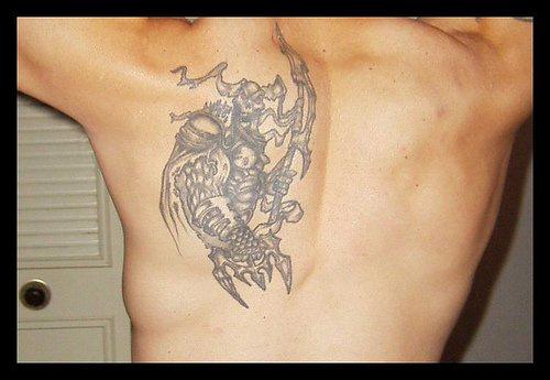 Iron tattoo robot with gun on upper back