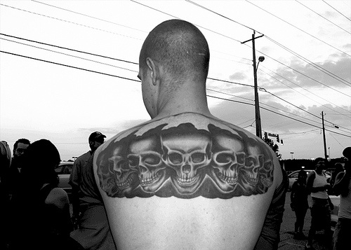On upper back row of black skulls tattoo