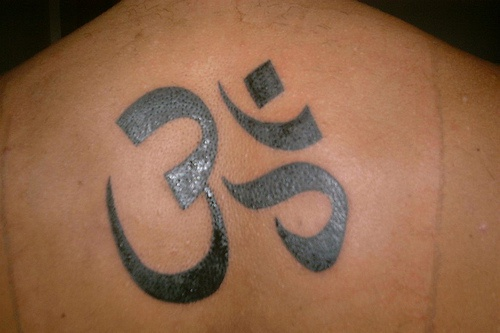 Black tattoo with sign hieroglyph on upper back