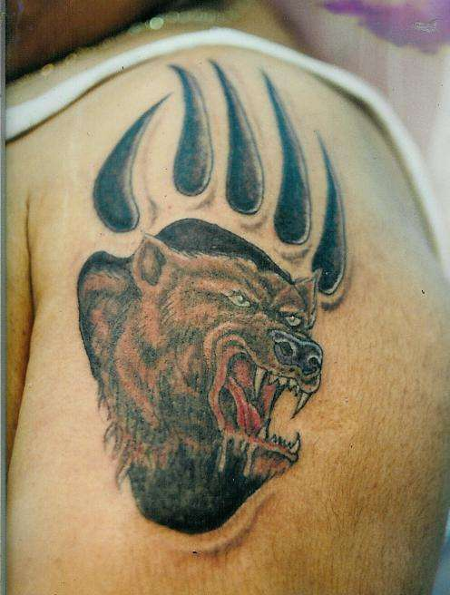 Angry bear in paw print tattoo