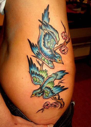 Tatuaggio colorato sul braccio gli uccelli sul ramo