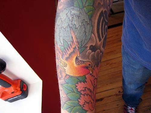 Tatuaje en el brazo, diseño de ave entre flores