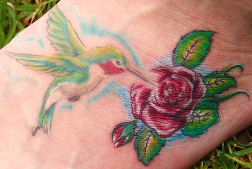 Colourful hummingbird on rose tattoo
