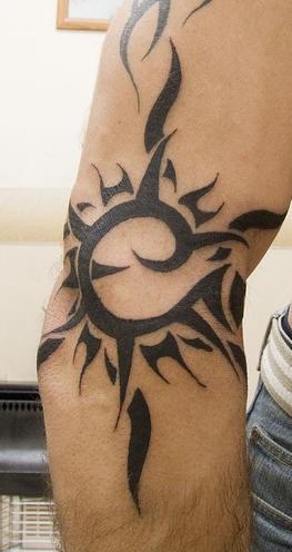Black sun tribal tracery tattoo