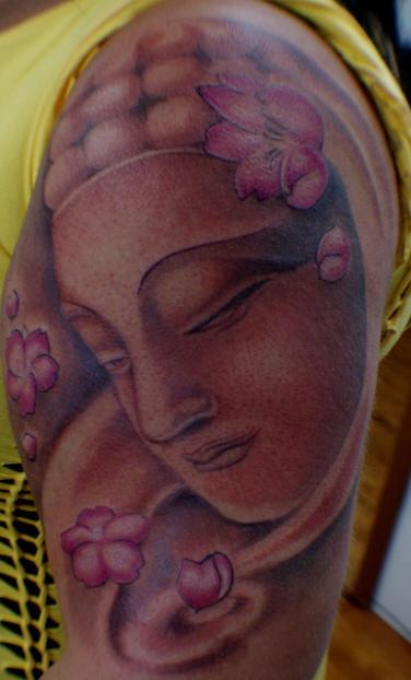 Stone buddha in flowers arm tattoo
