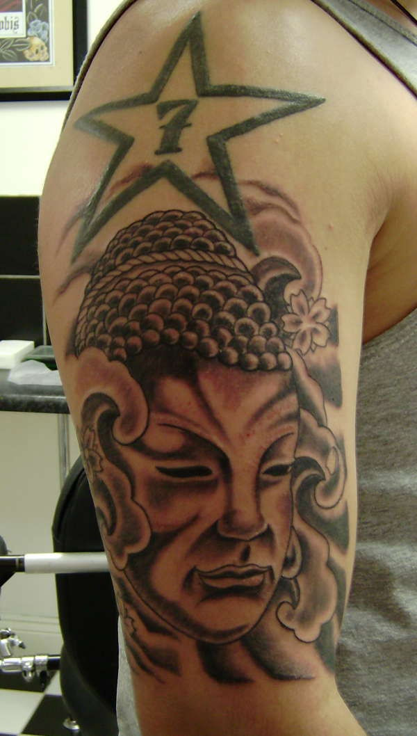 Stone buddha face with star under soulder tattoo