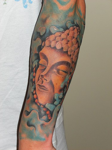 Stone buddha coloured sleeve tattoo