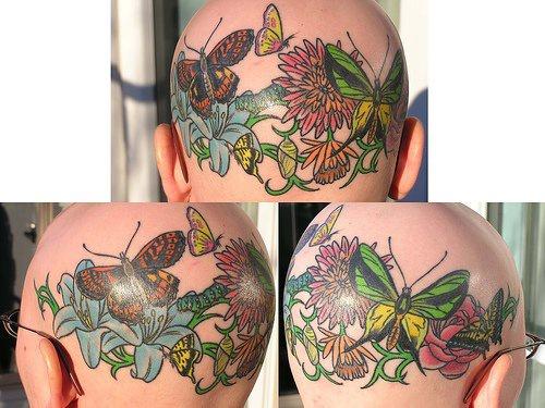 Tatuaggio pittoresco sulla testa in stile floristico colorato : le farfalle, i fiori, l&quoterba e gli insetti