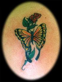 Monarch butterfly on red rose tattoo