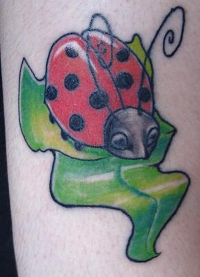 favolosa coccinella sulla  foglia verde tatuaggio