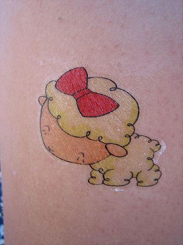 Carino agnello con fiocco di animazione tatuato