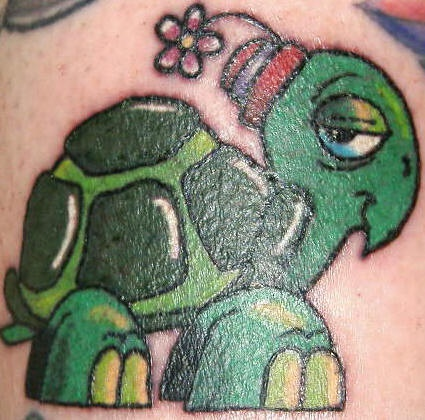 Tattoo of green cartoon turtle in hat with flower