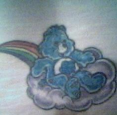 Blue bear riding on cloud in rainbow tattoo