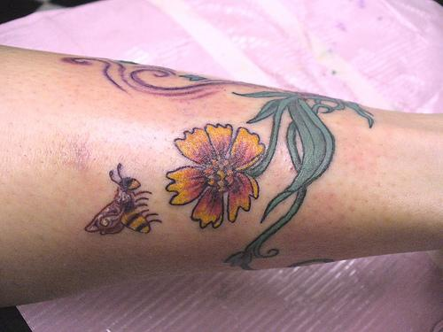 Tree tattoo with yellow flower and bee