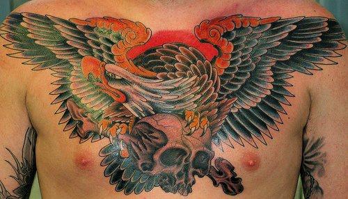 Bird carrying a skull chest tattoo