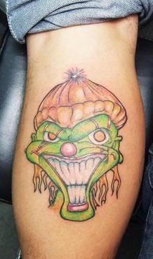 pagliaccio verde con sorriso tatuaggio sulla gamba