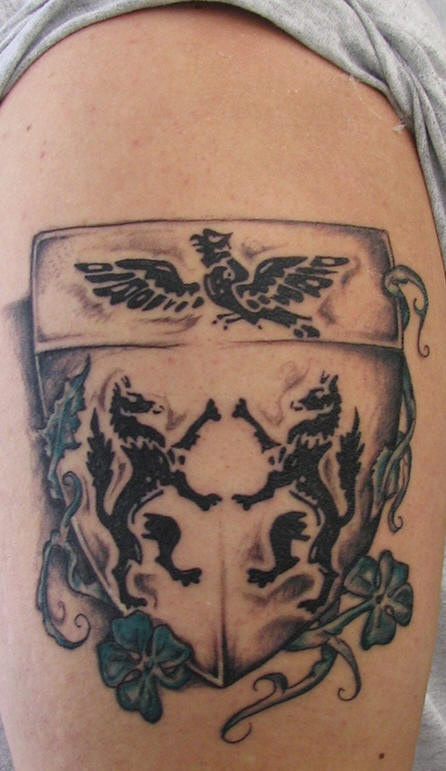 Shoulder tattoo, coat of arms,two standing wolfs, an eagle, plant