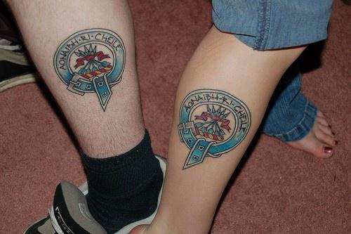 simbolo di famiglia colorato tatuaggio sulla gamba