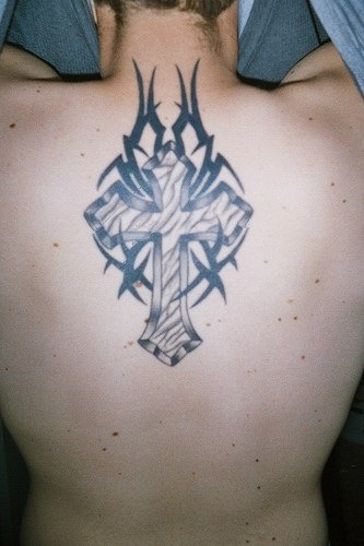 Cross with tribal tracery  tattoo