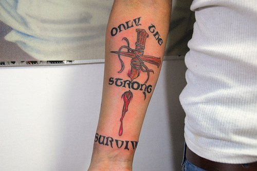 Bloody cross with thorns arm tattoo
