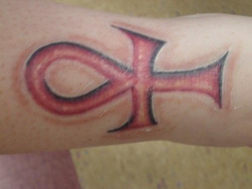 ankh rosso tatuaggio sul braccio