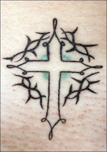Minimalistic cross with tribal tracery tattoo