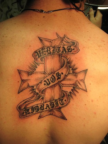 Latin writings on stripe around cross tattoo