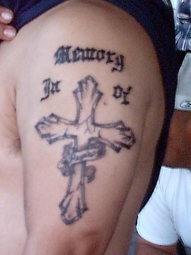 Memorial cross tattoo on arm