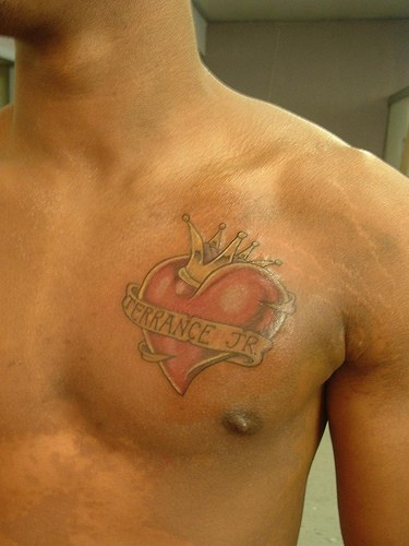 Crowned heart chest tattoo