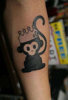 Black monkey in crown tattoo