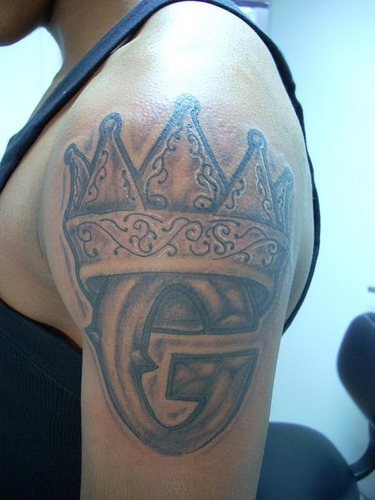 Crown with monogram tattoo on shoulder