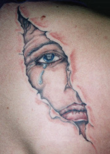 Crying face behind skin rip tattoo