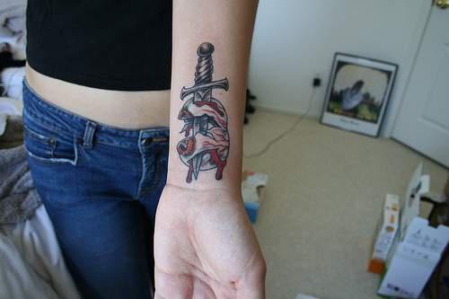 pugnale con bulbo oculare su di asso tatuaggio sul polso