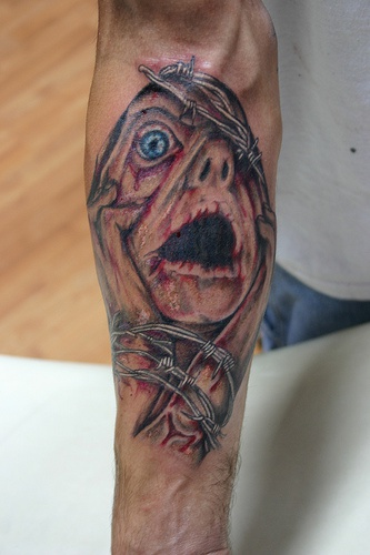 Death in agony arm tattoo
