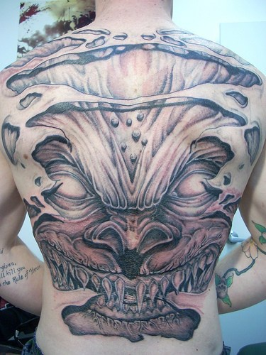 Sharp toothed devil full back tattoo