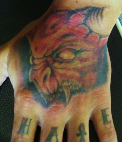 Hate, toothy,dreadful,awful devil demon hand tattoo